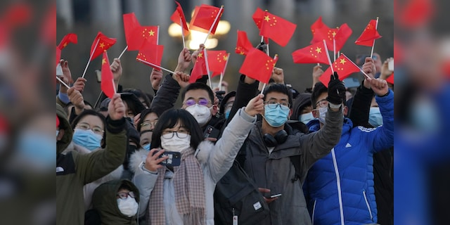 In this photo released by Xinhua News Agency, visitors to Tiananmen Square wave Chinese national flags as they attend the flag raising ceremony on Tiananmen Square in Beijing Friday, Jan. 1, 2021. (Ju Huanzong/Xinhua via AP)