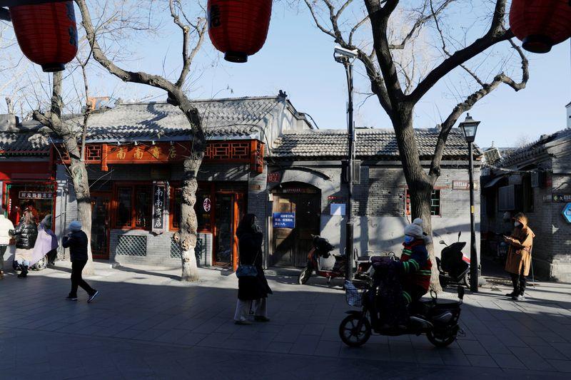 © Reuters. People wearing protective masks walk along Nanluoguxiang alley following the coronavirus disease (COVID-19) outbreak in Beijing