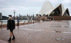 A man wearing a face mask walks in front of the Opera House on December 31, 2020.