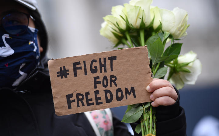 A protester holds a small placard at an event organised by Justitia Hong Kong to mourn the loss of Hong Kong's political freedoms