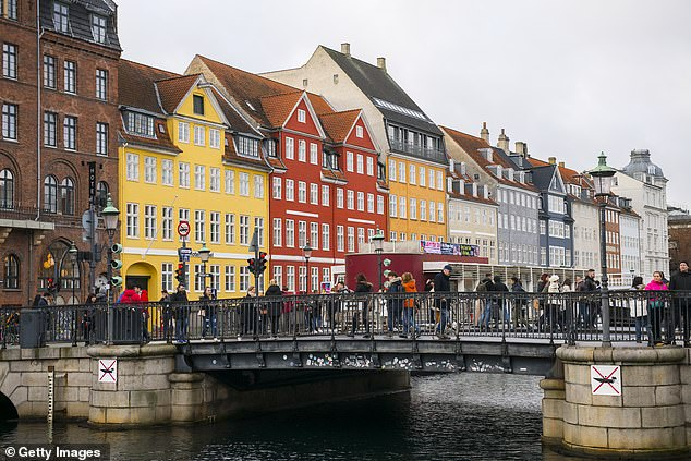 Prospective homeowners in Denmark can get a 20-year mortgage at a fixed interest rate of zero per cent (pictured, buildings overlooking the old harbour in Copenhagen)