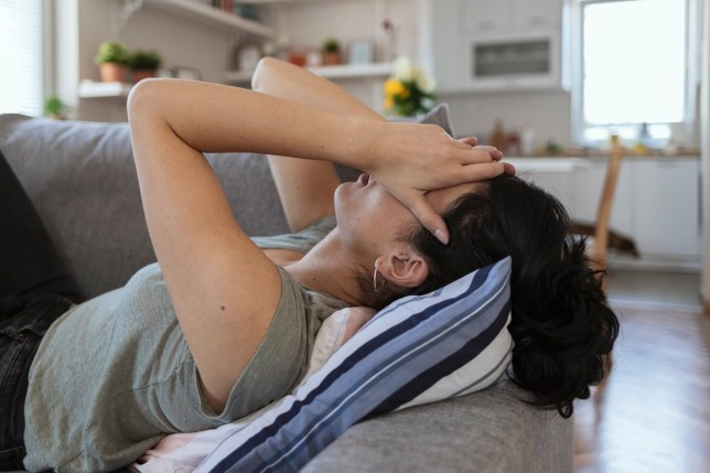 Young woman looking stressed out with head in hands