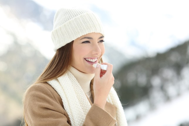 Portrait of a happy woman applying lip balm in winter with a snowy mountain in the background