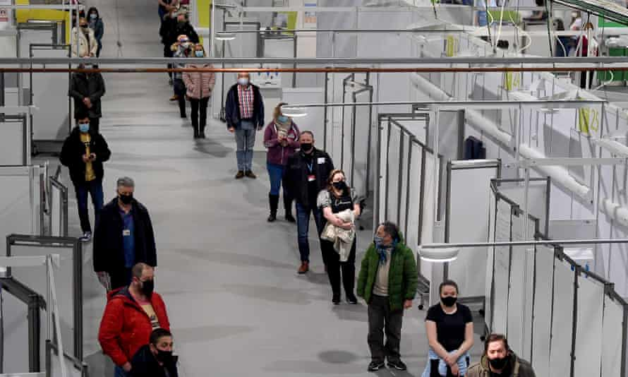 NHS staff and key workers queue for the coronavirus vaccine in Glasgow, Scotland.