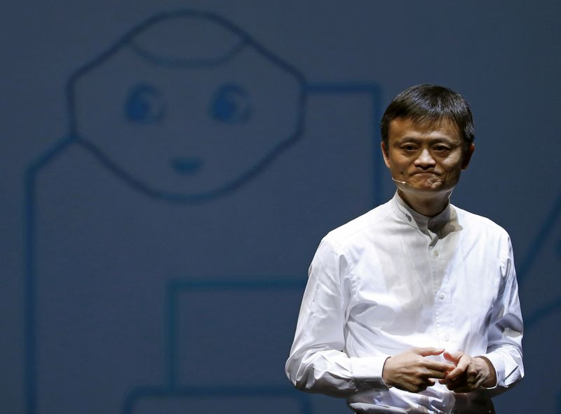 © Reuters. FILE PHOTO - Jack Ma, founder and executive chairman of China's Alibaba Group, speaks in front of a picture of SoftBank's human-like robot named 'pepper' during a news conference in Chiba
