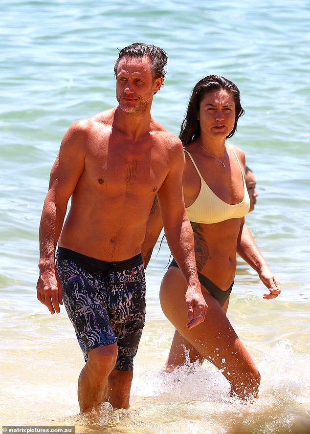 Hot couple:Jackie O's ex-husband Lee Henderson (left) enjoyed a loved-up beach date with his heavily tattooed partner Gabriella Motta in Sydney's Camp Coveon Sunday