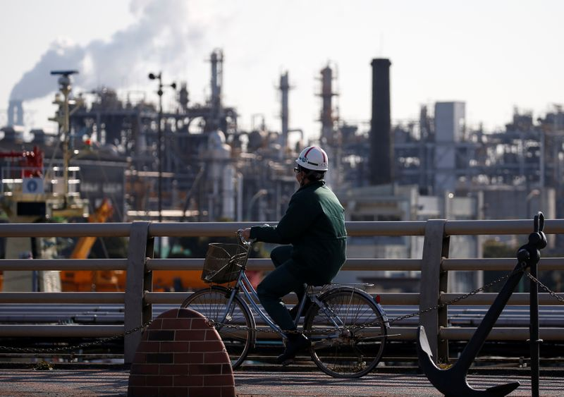 © Reuters. A worker cycles near a factory at the Keihin industrial zone in Kawasaki