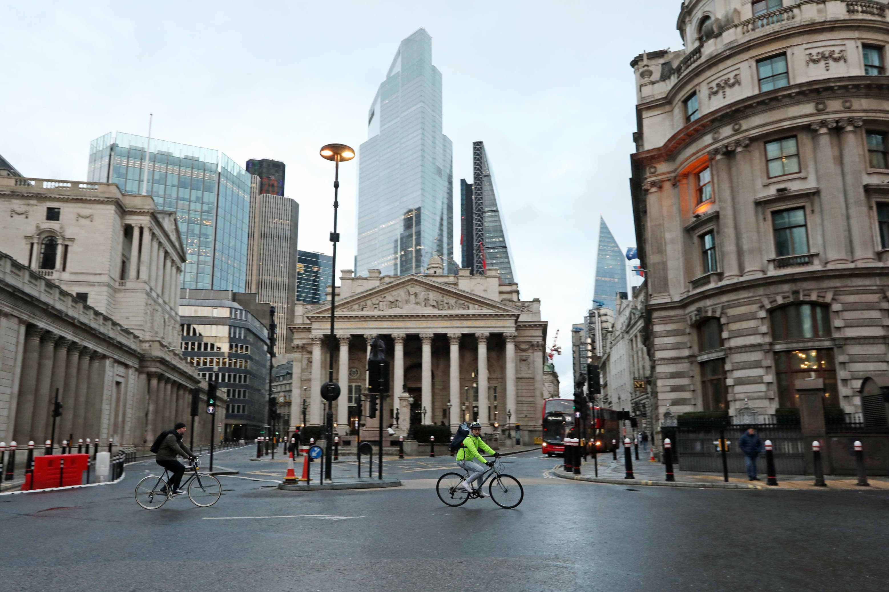 <p>Cyclists pass through an almost-deserted Bank junction in the heart of the City of London&nbsp;</p>