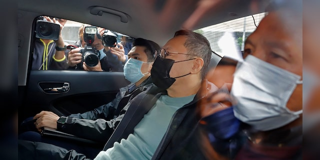 Former law professor Benny Tai, center, a key figure in Hong Kong's 2014 Occupy Central protests and also was one of the main organizers of the primaries, sits in a car after being arrested by police in Hong Kong, Wednesday, Jan. 6, 2021. (Associated Press)