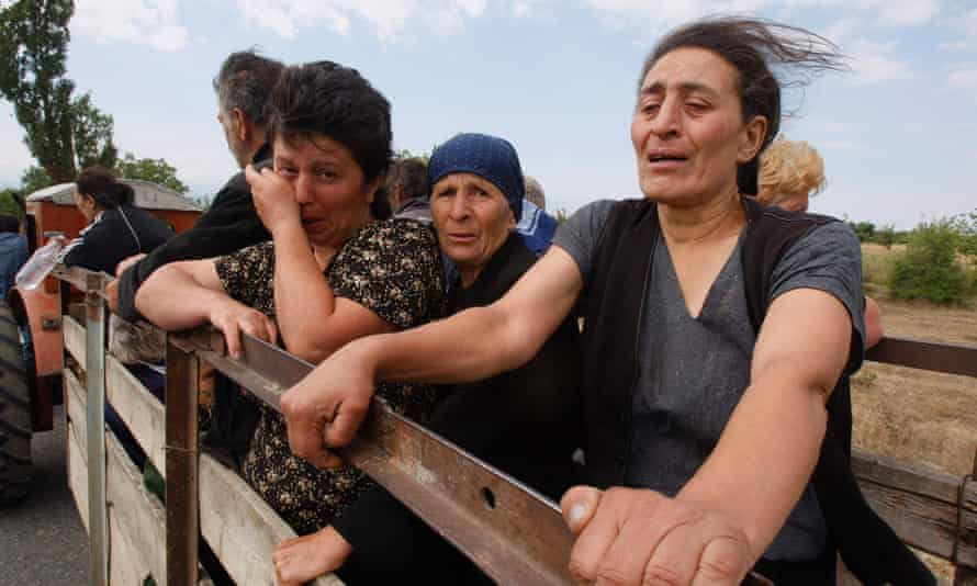 Georgian women cry as they leave their village near the town of Tskhinvali, Georgia, 10 August 10 2008.