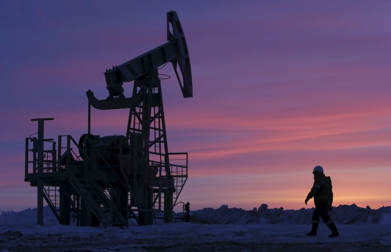 © Reuters. File photo of a worker walking past a pump jack on an oil field owned by Bashneft company near Nikolo-Berezovka
