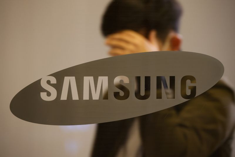 © Reuters. A man walks past the logo of Samsung at its office building in Seoul