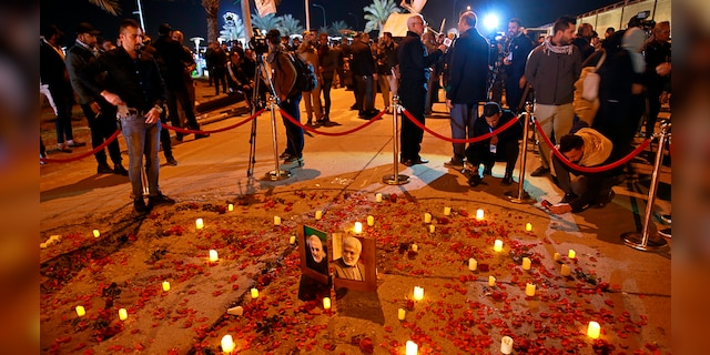 Popular Mobilization Forces and their supporters light candles at Baghdad's international airport on Saturday, Jan. 2, 2021, on the anniversary of the killing of Abu Mahdi al-Muhandis, deputy commander of the PMF and Gen. Qassem Soleimani, head of Iran's Quds forces. (Associated Press)