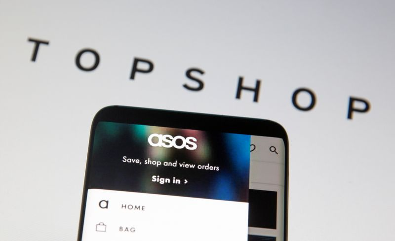 © Reuters. Asos logo is seen in a smartphone in front of a displayed TopShop logo in this illustration