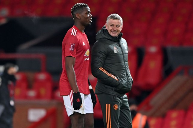 Manchester United's Norwegian manager Ole Gunnar Solskjaer (R) speaks with Manchester United's French midfielder Paul Pogba (L) as they leave after the English FA Cup fourth round football match between Manchester United and Liverpool at Old Trafford in Manchester, north west England, on January 24, 2021. - Manchester United won the game 3-2.