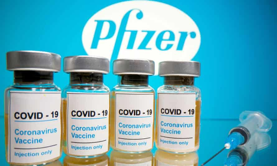 "Vials with a sticker reading, ""COVID-19 / Coronavirus vaccine / Injection only"" and a medical syringe are seen in front of a displayed Pfizer logo."