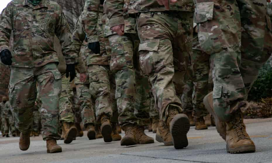 National guard troops march towards the Capitol on inauguration day, 20 January. The armed forces are now having to confront the prospect of far-right extremism within their own ranks.