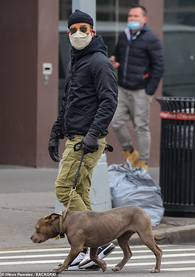 City stroll:Slipping some airpods into his ears, he was seen with the dog's leash tied around his waist to keep her close