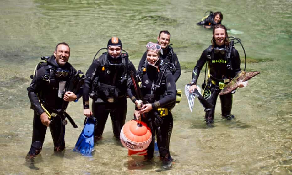 Divers coming out of the water with gear in Portugal