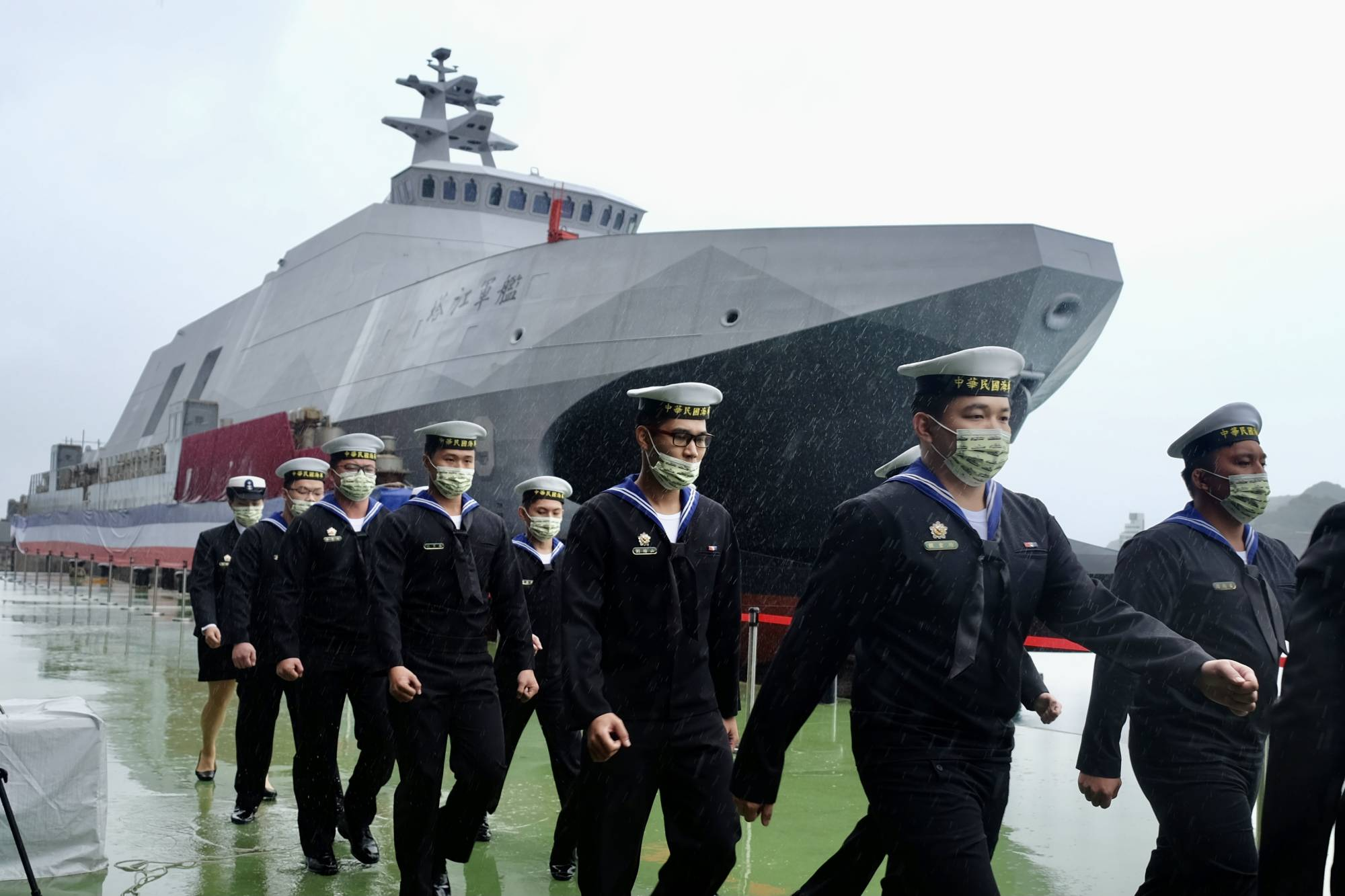 Taiwanese Navy sailors walk past a domestically built Tuo Chiang-class corvette during an official ceremony at a shipyard in Suao, Taiwan, on Dec. 15, 2020. | AFP-JIJI