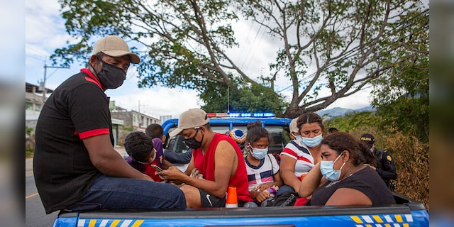Honduran migrants sit in the bed of a police vehicle after they were detained in Chiquimula, Guatemala, Tuesday, Jan. 19, 2021. (AP Photo/Oliver de Ros)