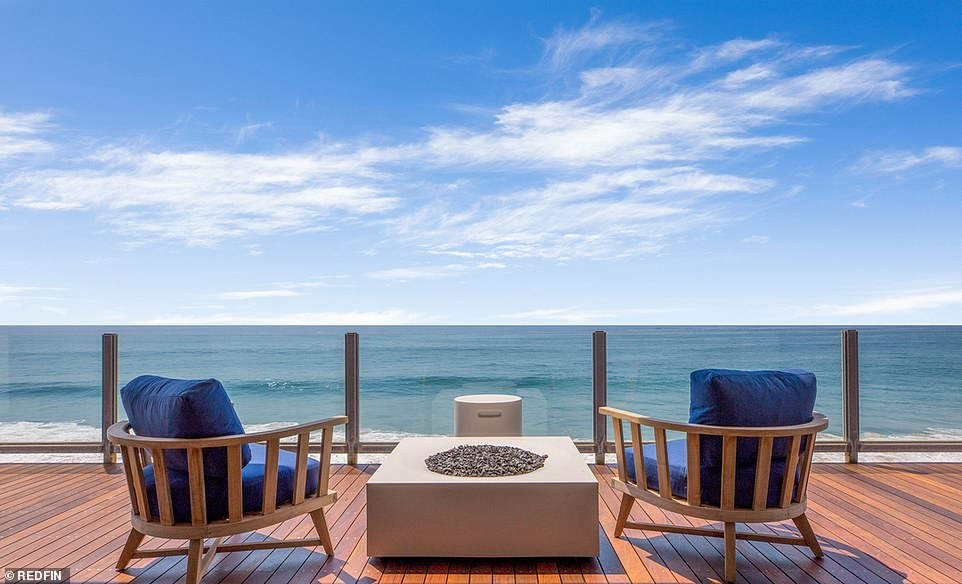 Beach views: The master suite also spills out through floor-to-ceiling sliding windows to its own private balcony, overlooking the serene ocean