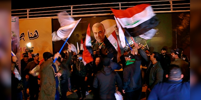 Popular Mobilization Forces and their supporters chant slogans against the United States at Baghdad's international airport on Saturday, Jan. 2, 2021, on the anniversary of the killing of Abu Mahdi al-Muhandis, deputy commander of the PMF and Gen. Qassem Soleimani, head of Iran's Quds forces in a U.S. airstrike. (Associated Press)