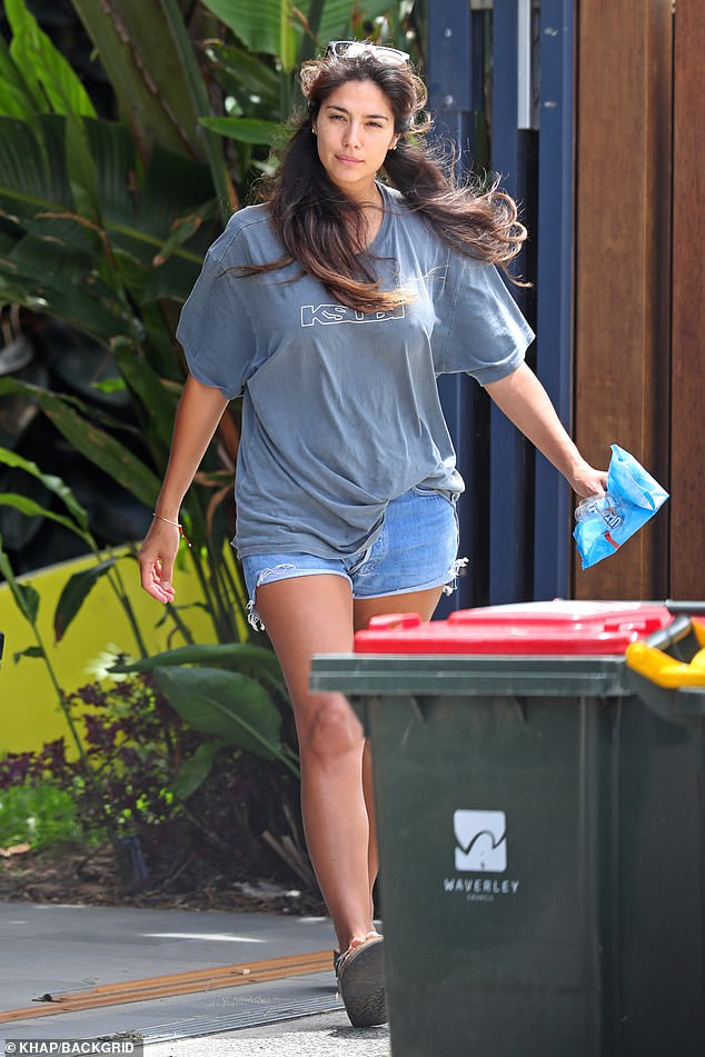 Hard at work: Dressed down in a baggy T-shirt and denim shorts, Pia was seen collecting empty food packets from the back of her car, before throwing them into a nearby bin
