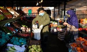 Saki Hussain helps a customer at Longsight market in Manchester.