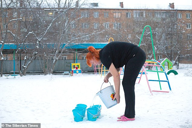 A teacher at state school 317 fills up a bucket of the freezing-cold water for the children to douse themselves with in Siberia, Russia