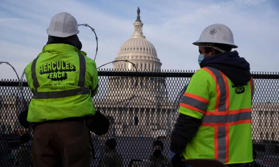 Workers install razor wire atop fencing outside the US Capitol ahead of Biden's inauguration.