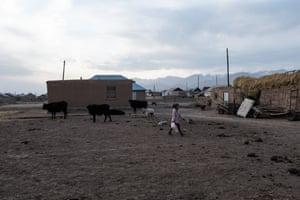Girl carries water bottles in Sary-Mogol.