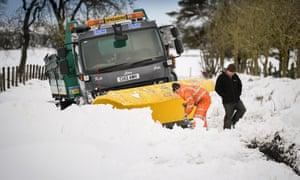 Men clear snow around a plough stuck in a drift in Lamancha, Scotland