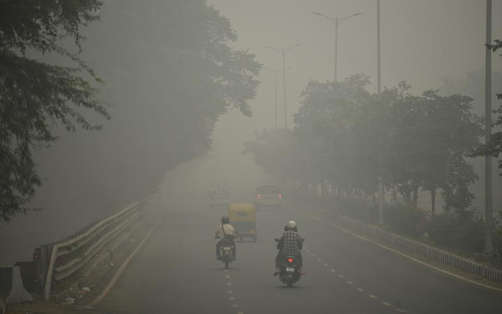 Motorists drive along a road under heavy smog conditions, in New Delhi on 3 November, 2019.
