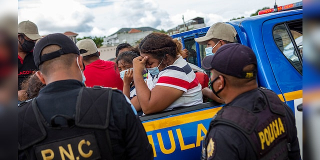 A Honduran migrant woman trying to reach the U.S. cries after she was detained in the Guatemalan department of Chiquimula, Tuesday, Jan. 19, 2021. (AP Photo/Oliver de Ros)