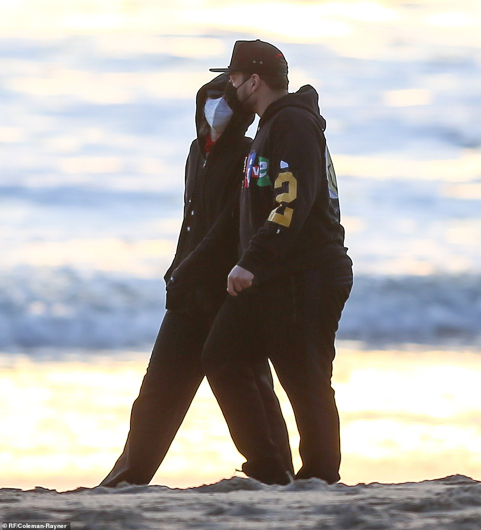Scoping it out:As sunset approached, Miley and Bradley ceased their sandy stroll in order to to scope out a viewing spot