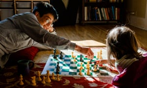 A smiling Dad lays on floor with little girl playing chess in sunshineGettyImages-1226029058