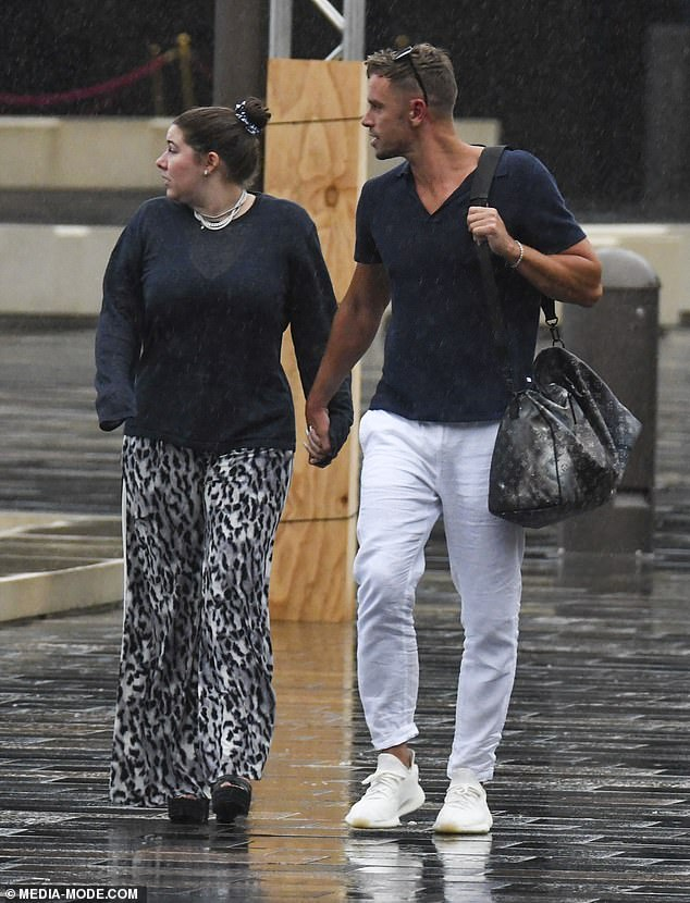 Romance: The couple walked hand-in-hand in the rain after disembarking the cruise on Sydney Harbour together