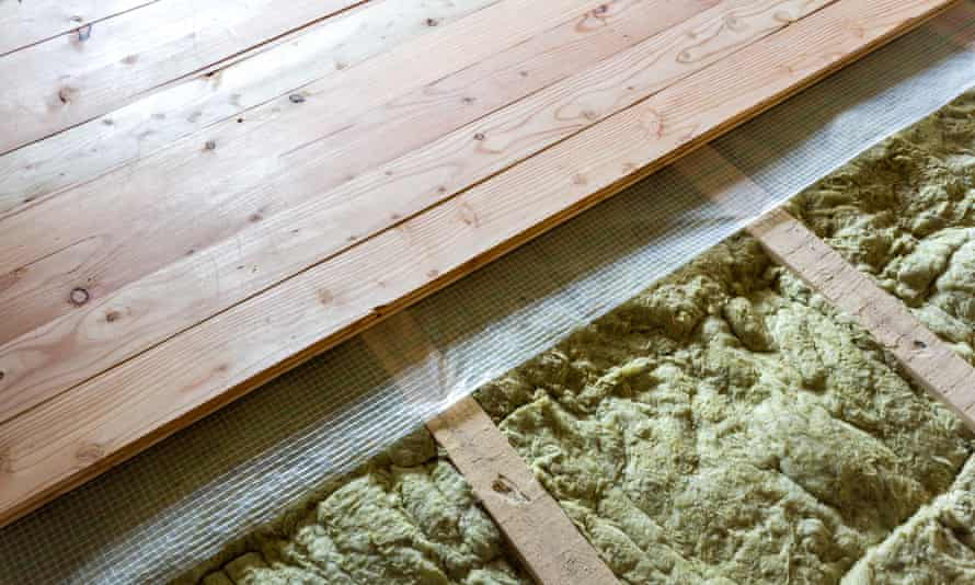 Installation of a floor of wooden natural planks and mineral wool insulation.