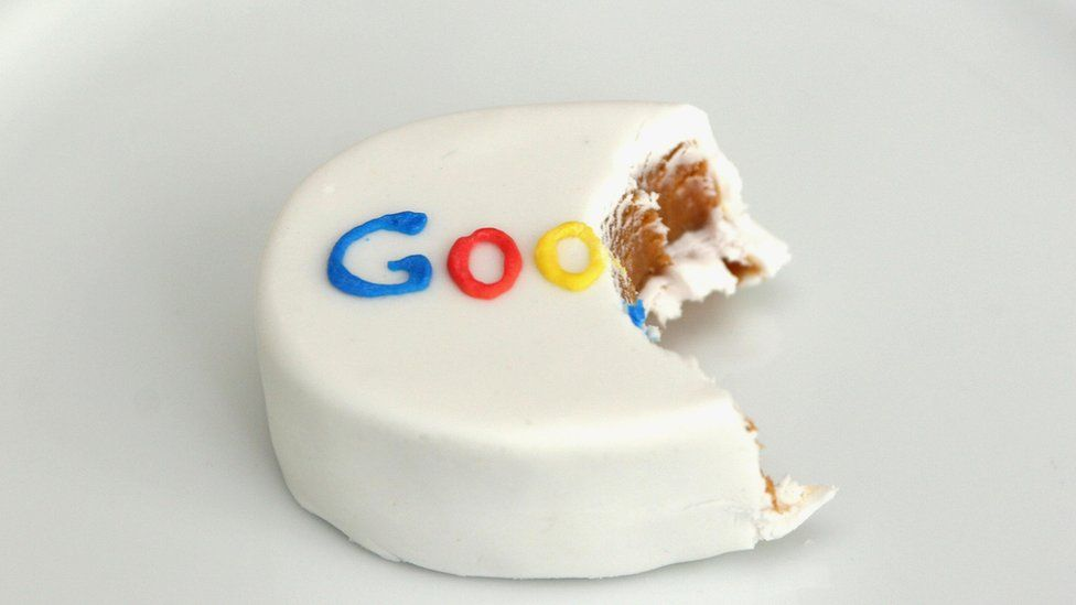 A small hand-sized cake with a bite taken out of it - and the Google logo in icing on top - is seen in this photo