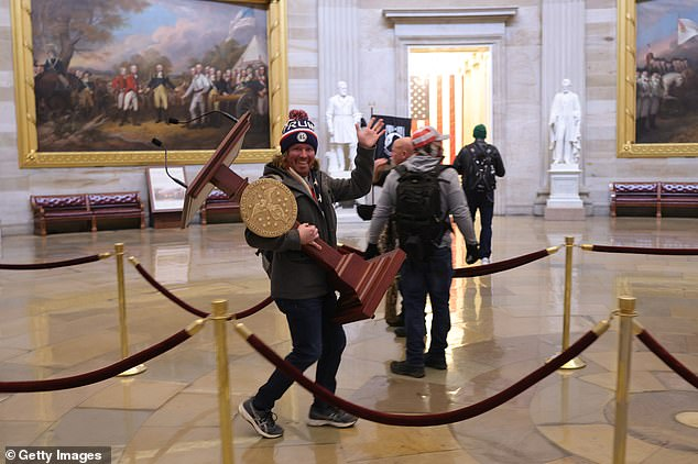 A protester walks through Congress carrying Nancy Pelosi's lectern after storming the Capitol