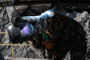 Ali Umarov fixes an excavator in the coalmine near Sary-Mogol.