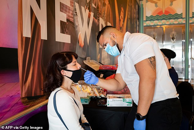 "When the model was shifted to assuming patients were most contagious on day 4, researchers found 67% of all spread was asymptomatic. Pictured: A person gets tested for COVID-19 before working on the play Seven Deadly Sin"" at Lincoln Road in Miami Beach, Florida, December 23"