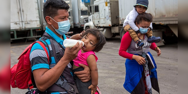 Honduran migrants walk to the border crossing after being transported in an army truck to El Florido, Guatemala, a border point between Guatemala and Honduras, Tuesday, Jan. 19, 2021. (AP Photo/Oliver de Ros) 03104