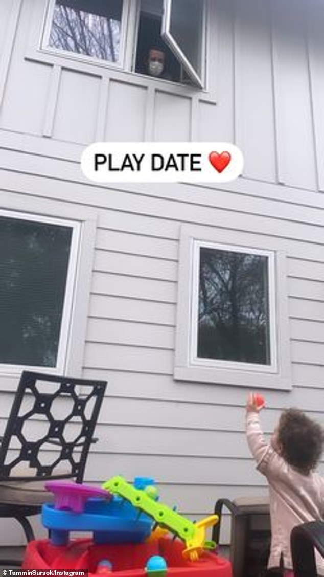 Touching:She then shared a heartbreaking image of her husband peeking out of the second story window to see their daughter, which she captioned: 'Play date'