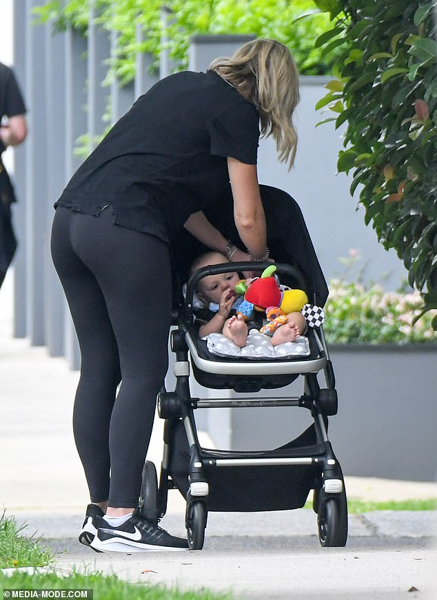 Doting: At one point, Sylvia could be seen attending to her son as they walked around, who had some toys in the pram to keep him entertained