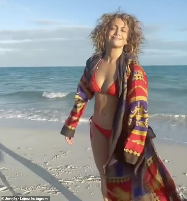 Beach babe on the loose: In the new clip, Jennifer is smiling with her chin up as she walks then dances on the shore in Miami