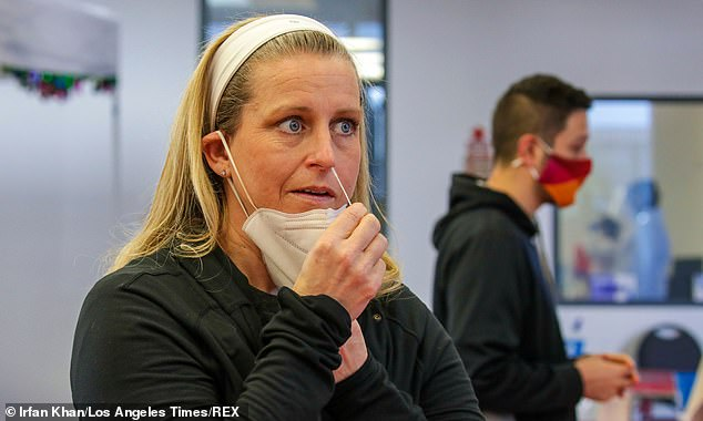 They determined 46,910,006 people had been infected with coronavirus by November 15 - or more than 14% of Americans. Pictured:Shayleen Ojeda uses a nasal swab for a COVID-19 test in Ontario, California, December 2020