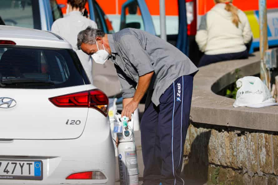 A medic administers oxygen to a Covid-19 patient in their car at the Domenico Cotugno hospital in Naples, early November last year, as the facility had run out of space.
