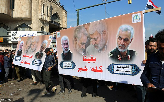 Supporters of Iran-backed Iraqi Shiite Popular Mobilization Forces in Baghdad on Monday hold the picture of Qasem Soleimani and Iraqi militia commander Abu Mahdi al-Muhandis who were killed by a US drone last year